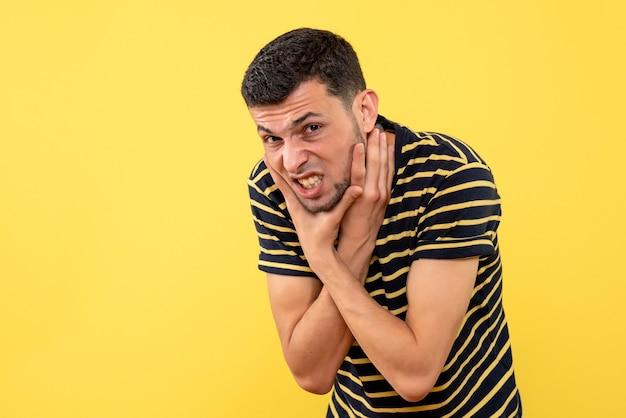 Vista frontale bel maschio in t-shirt a righe bianco e nero che tiene la gola su sfondo giallo isolato