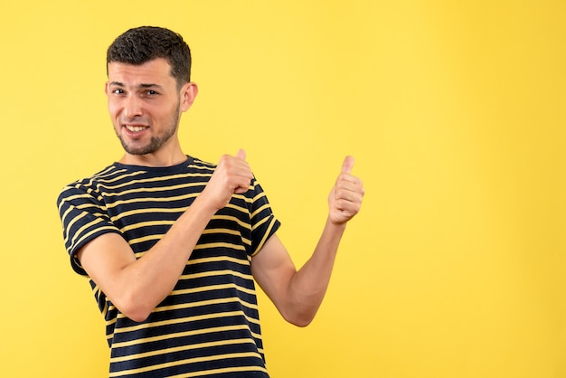 Front view handsome male in black and white striped t-shirt pointing at back on yellow isolated background