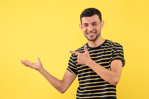 Front view handsome male in black and white striped t-shirt pointing at left on yellow isolated background