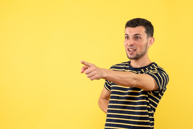 Front view handsome male in black and white striped t-shirt pointing at something yellow isolated background