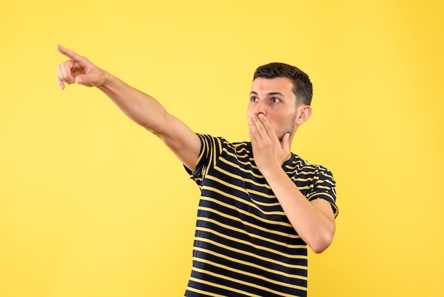 Vista frontale bel maschio in maglietta a righe in bianco e nero che punta con il dito qualcosa su sfondo giallo isolato