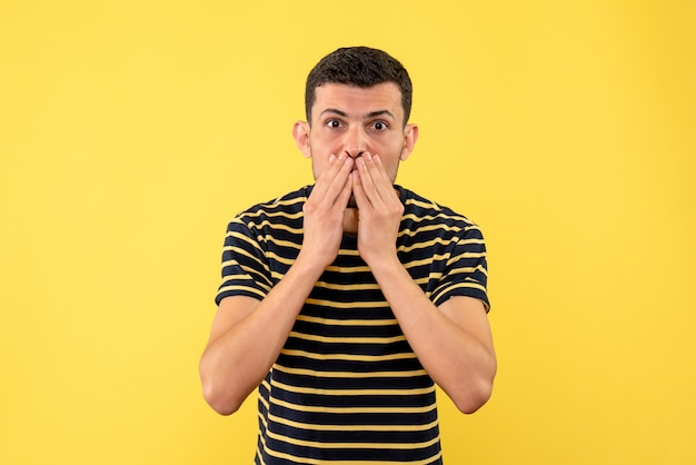 Front view handsome male in black and white striped t-shirt putting hands on face on yellow isolated background