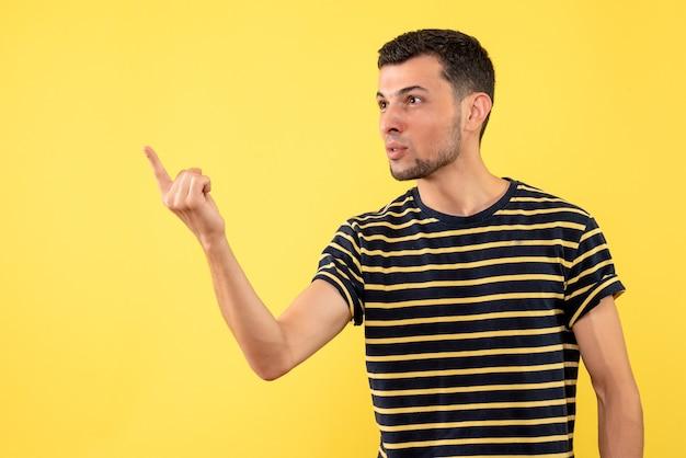 Vista frontale bel maschio in maglietta a righe bianco e nero in piedi su sfondo giallo isolato