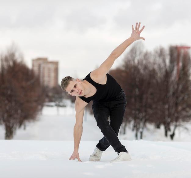 Vista frontale del ballerino maschio bello fuori con neve