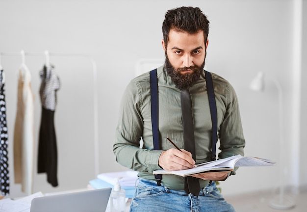 Front view of handsome male fashion designer in atelier with papers