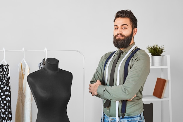 Front view of handsome male fashion designer posing in atelier with dress form