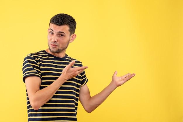 격리 된 노란색 배경에 뭔가 보여주는 흑백 줄무늬 티셔츠에 전면보기 잘 생긴 남성