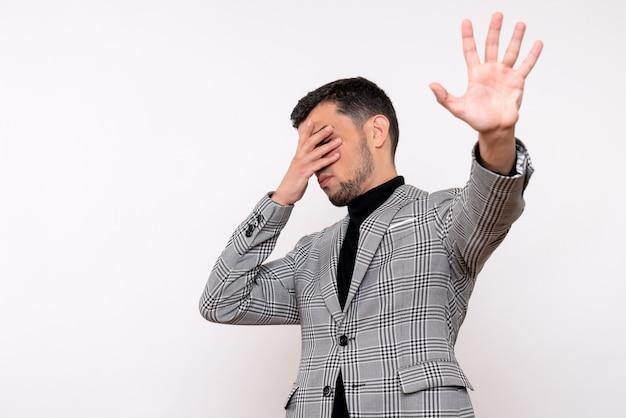 白い背景の上に一時停止の標識を作る目を覆っているスーツのハンサムな男性の正面図
