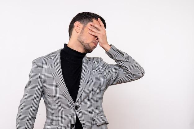 白い背景の上に立っている手で目を覆うスーツのハンサムな男性の正面図