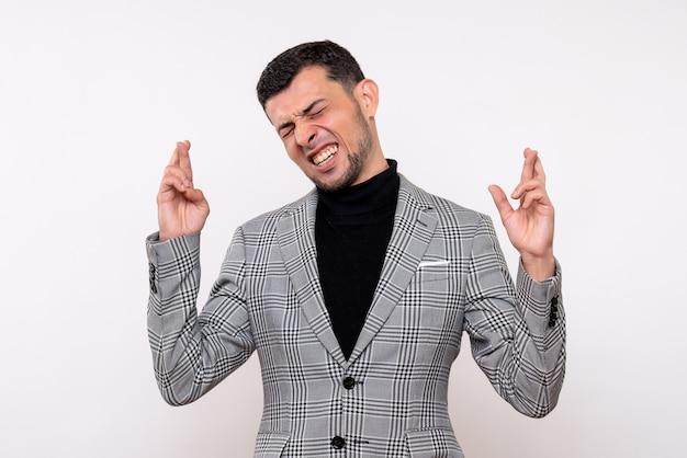 白い背景の上に立って幸運のジェスチャーを作るスーツの正面図ハンサムな男性