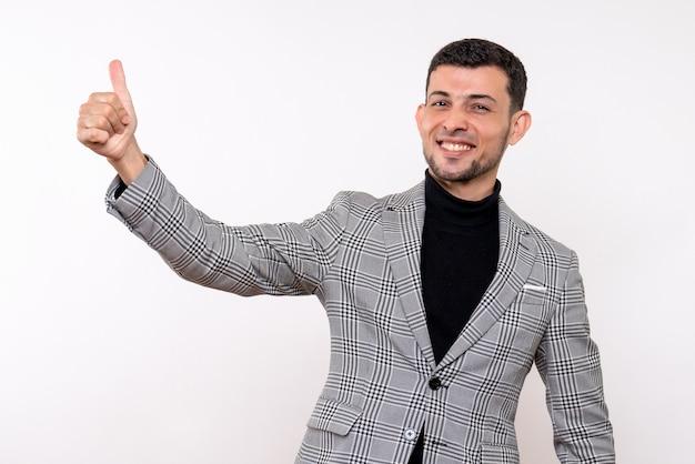 Вид спереди красивый мужчина в костюме, делая большой палец вверх знак, стоящий на белом фоне