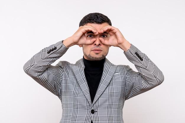 白い背景の上に立っている彼の目の前に双眼鏡を置くスーツの正面図ハンサムな男性