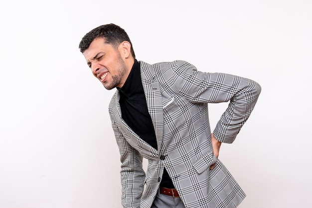 Front view handsome male in suit holding his back with pain standing on white background