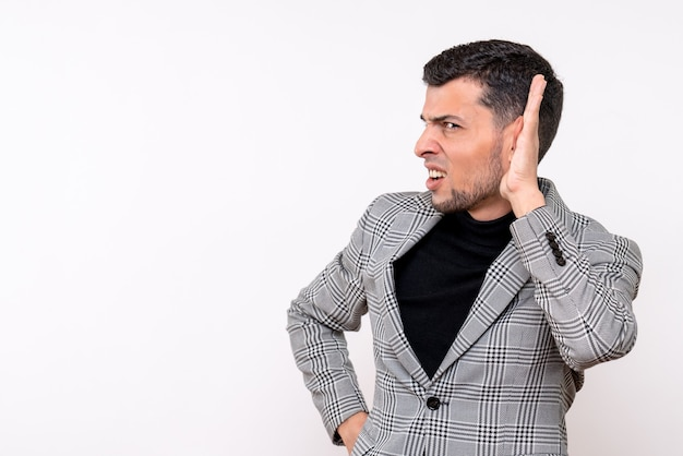 Vista frontale bel maschio in tuta ascoltando qualcosa in piedi su sfondo bianco isolato