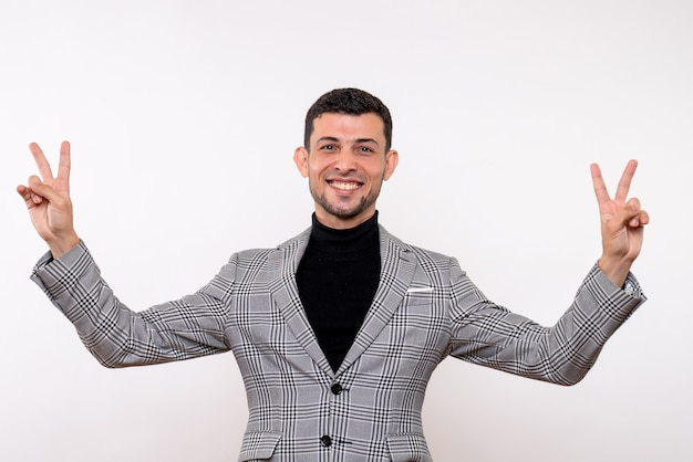 Front view handsome male in suit making victory sign standing on white background