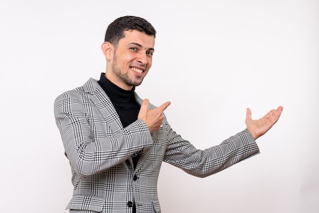Front view handsome male in suit pointing at behind standing on white background