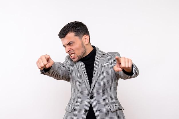 Vista frontale bel maschio in tuta che punta con la fotocamera dito in piedi su sfondo bianco