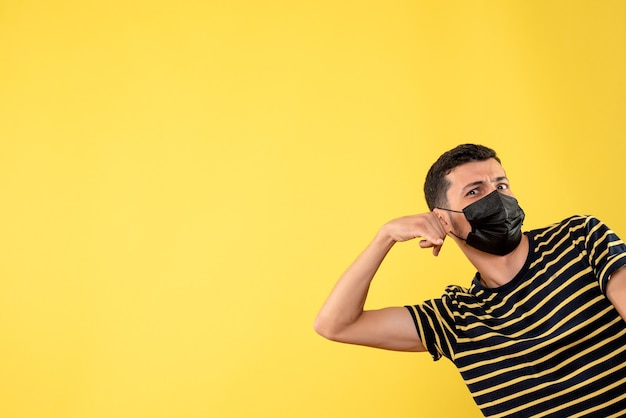 Front view handsome man in black mask making call me sign yellow isolated background