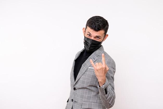 Vista frontale bell'uomo in maschera nera che fa segno di roccia in piedi su sfondo bianco isolato