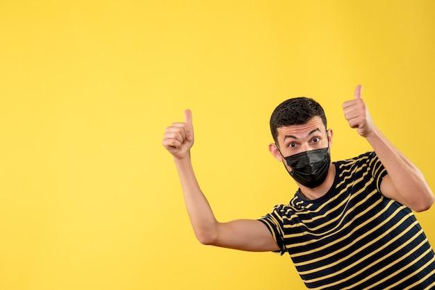 Vista frontale bell'uomo in maschera nera che fa il pollice sul segno giallo su sfondo isolato