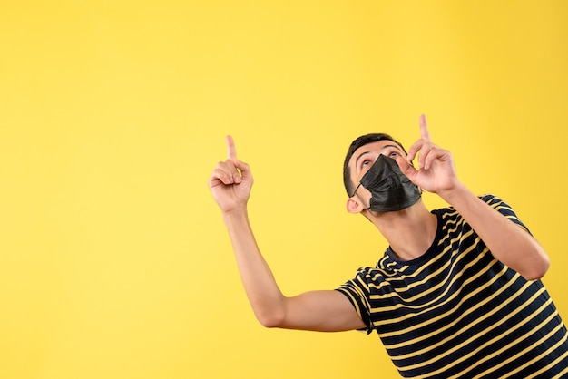Front view handsome man in black mask pointing at ceiling on yellow isolated background