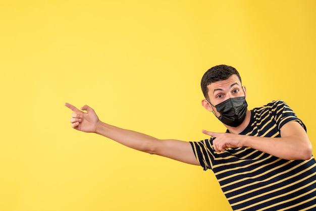 Vista frontale bell'uomo in maschera nera che punta a sinistra sfondo giallo isolato