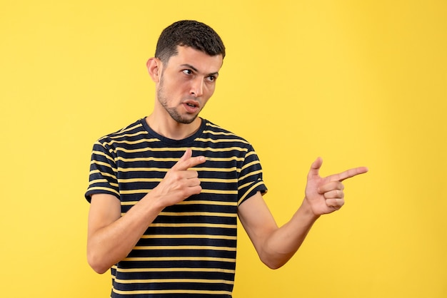 Vista frontale bell'uomo in maschera nera che punta a qualcuno su sfondo giallo isolato