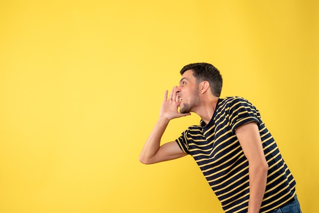 Front view handsome man in black and white striped t-shirt calling someone on yellow isolated background