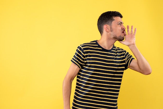 Front view handsome man in black and white striped t-shirt calling someone yellow isolated background