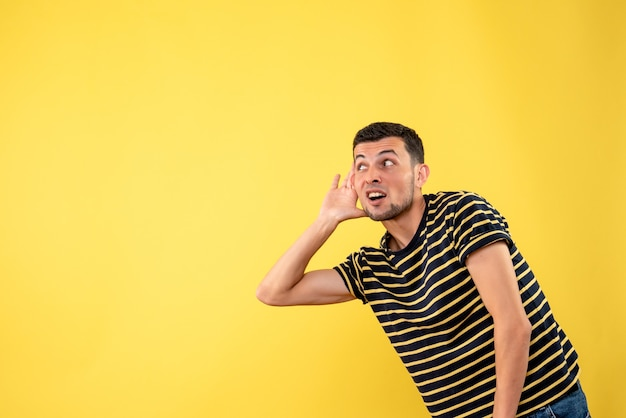 Front view handsome man in black and white striped t-shirt listening at something on yellow isolated background