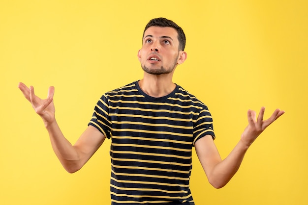 Front view handsome man in black and white striped t-shirt looking at ceiling on yellow isolated background