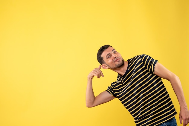 Front view handsome man in black and white striped t-shirt making call me phone gesture on yellow isolated background
