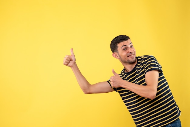 Front view handsome man in black and white striped t-shirt making thumb up sign on yellow isolated background
