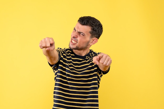 Front view handsome man in black and white striped t-shirt showing winning gesture on yellow isolated background