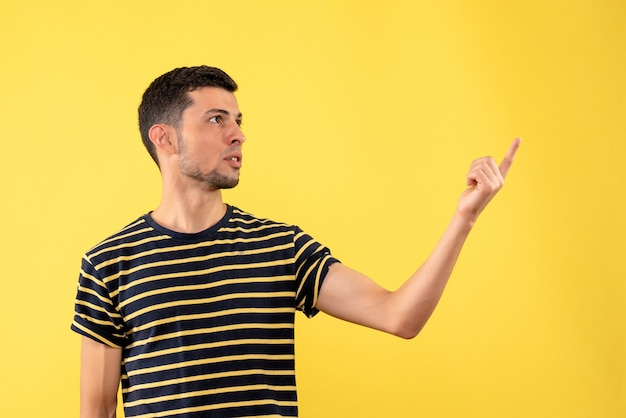 Front view handsome man in black and white striped t-shirt standing on yellow isolated background