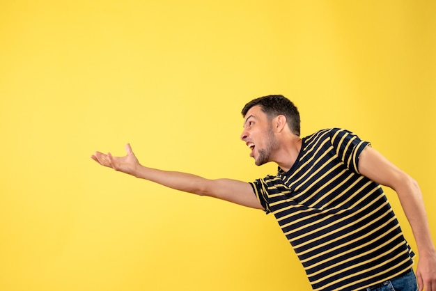 Front view handsome man in black and white striped t-shirt trying to catch something on yellow isolated background