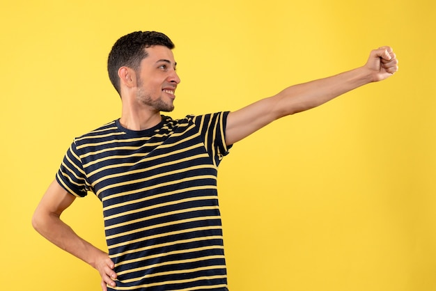 Front view handsome man in black and white striped t-shirt yellow isolated background