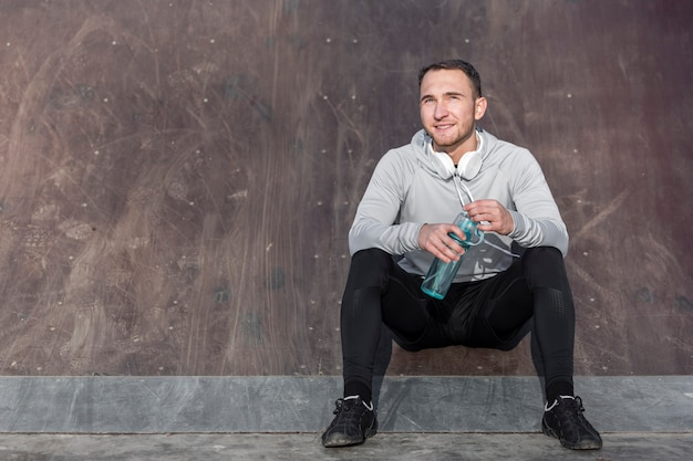 Front view handsome man holding a bottle of water