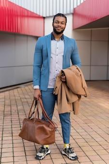彼のバッグを保持している正面ハンサムな男
