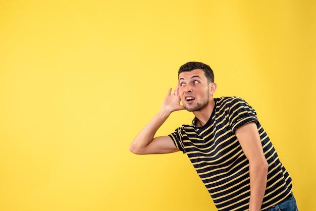 黄色の孤立した背景で何かを聞いている黒と白の縞模様のtシャツの正面図ハンサムな男