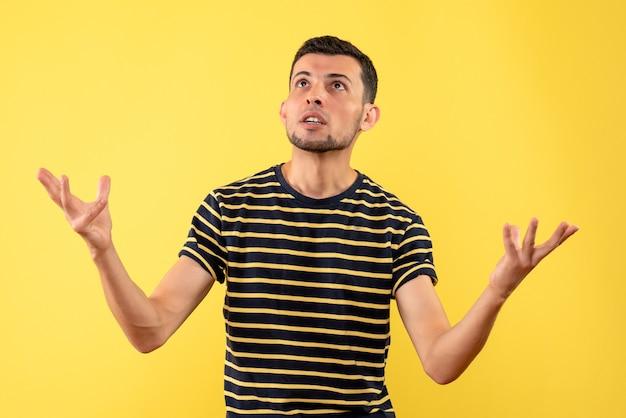 黄色の孤立した背景の天井を見て黒と白の縞模様のtシャツの正面図ハンサムな男