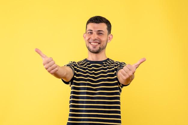 黄色の孤立した背景に親指を立てる黒と白の縞模様のtシャツの正面図ハンサムな男