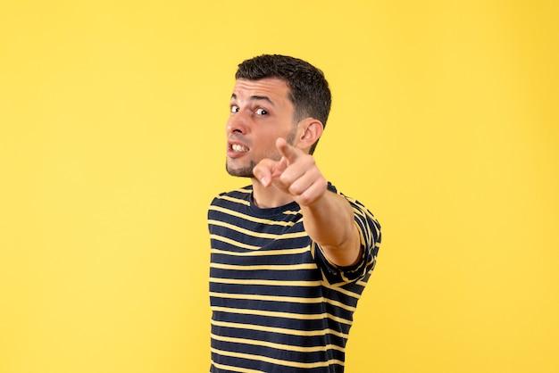 黄色の孤立した背景の上のカメラを指している黒と白の縞模様のtシャツの正面図ハンサムな男