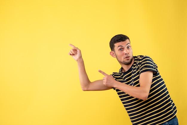 黄色の孤立した背景に何かを指している黒と白の縞模様のtシャツの正面図ハンサムな男