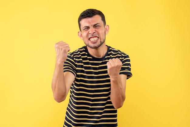 黄色の孤立した背景に勝利のジェスチャーを示す黒と白の縞模様のtシャツの正面図ハンサムな男