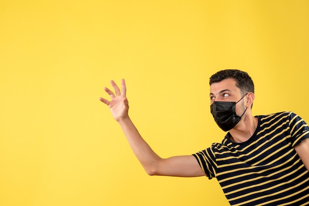 黄色の孤立した背景に誰かを歓迎する黒いマスクの正面図ハンサムな男