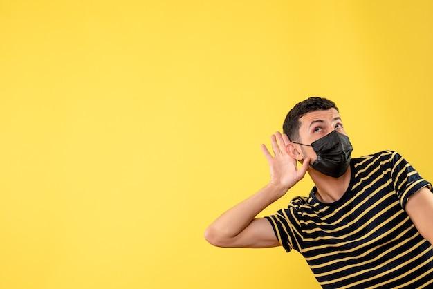 Вид спереди красивый мужчина в черной маске, слушая что-то желтое на изолированном фоне