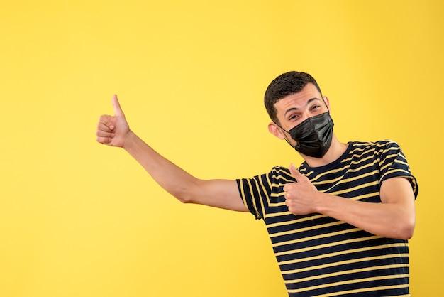黄色の孤立した背景に親指を立てる黒いマスクの正面図ハンサムな男