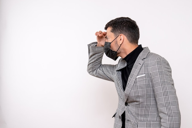 Вид спереди красивый мужчина в костюме, глядя на что-то стоящее на белом изолированном фоне