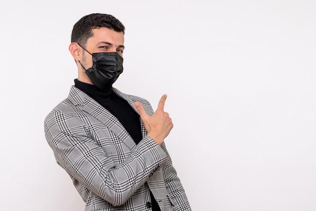 白い孤立した背景に立って後ろを指しているスーツの正面図ハンサムな男